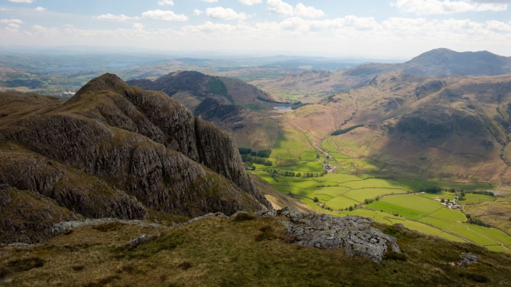 The mighty Gimmer Crag looms over the fields of Langdale